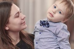 Schöne junge Mutter mit einem Baby in ihren Armen zu Hause Glückliche Familie und Mutterschaftskonzept stockfoto