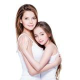 Schöne junge Mutter mit einer kleinen Tochter 8 Jahre umfassen eac stockfoto