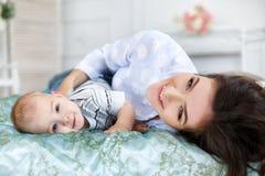 Schöne junge Mutter mit ihrem neugeborenen Babysohn, der auf Bett in ihrem Schlafzimmer liegt Lizenzfreie Stockfotos