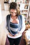 Schöne junge Mutter mit ihrem Sohn im Riemen stockfotos