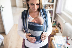 Schöne junge Mutter mit ihrem Sohn im Riemen stockfoto