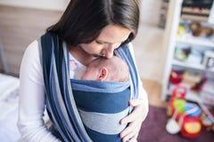 Schöne junge Mutter mit ihrem Sohn im Riemen stockbild
