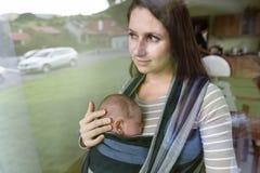 Schöne junge Mutter mit ihrem Sohn im Riemen stockfotografie