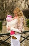 Schöne junge Mutter mit Schätzchentochter im Riemen stockfotografie