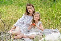 Schöne junge Mutter und ihre kleine Tochter im weißen Kleid, das Spaß in einem Picknick hat Sie sitzen auf einem Plaid auf dem Gr stockbilder