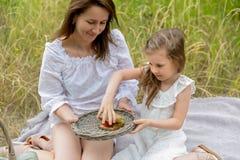 Schöne junge Mutter und ihre kleine Tochter im weißen Kleid, das Spaß in einem Picknick hat Sie sitzen auf einem Plaid auf dem Gr lizenzfreies stockbild