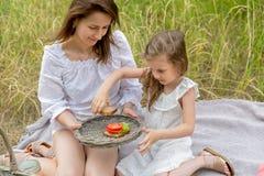 Schöne junge Mutter und ihre kleine Tochter im weißen Kleid, das Spaß in einem Picknick hat Sie sitzen auf einem Plaid auf dem Gr lizenzfreie stockfotos