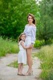 Schöne junge Mutter und ihre kleine Tochter im weißen Kleid, das Spaß in einem Picknick hat Sie stehen auf der Straße im Park und stockfotografie