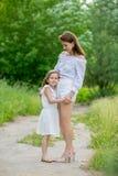 Schöne junge Mutter und ihre kleine Tochter im weißen Kleid, das Spaß in einem Picknick hat Sie stehen auf der Straße im Park und lizenzfreies stockfoto