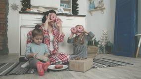 Schöne junge Mutter und ihre nette kleine Tochter spielen mit Plätzchenschneidern und lächeln beim Backen in der Küche an stock footage