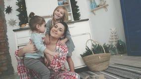 Schöne junge Mutter und ihre nette kleine Tochter spielen mit Plätzchenschneidern und lächeln beim Backen in der Küche an stock video footage