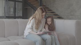 Schöne junge Mutter und ihre nette kleine Tochter verwenden eine Tablette und ein Lächeln und sitzen auf Sofa im großen Haus stock video footage