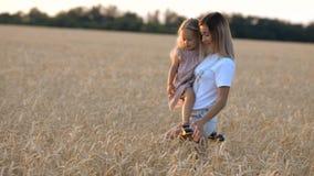 Schöne junge Mutter und ihre Tochter, die Spaß am Weizenfeld hat stock footage