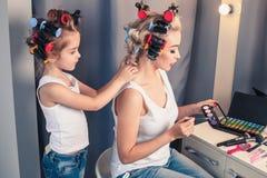 Schöne junge Mutter und ihre Tochter mit Haarlockenwicklern Lizenzfreies Stockfoto