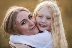 Schöne junge Mutter und ihre Tochter am Weizenfeld Lizenzfreies Stockfoto