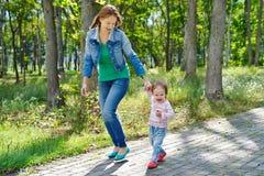 Schöne junge Mutter und lachende Tochter, die draußen ich geht Stockbilder