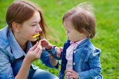 Schöne junge Mutter und Tochter, die draußen in Parkgras geht Lizenzfreie Stockfotos