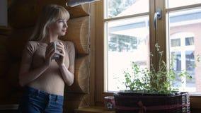 Schöne junge nachdenkliche Frau, die Schale heißen Tee hält und das Fenster bereitsteht Stockfotos