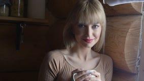 Schöne junge nachdenkliche Frau, die Schale heißen Tee hält und das Fenster bereitsteht Lizenzfreies Stockfoto