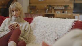 Schöne junge nachdenkliche Frau, die zu Hause Schale heißen Tee hält Stockfoto