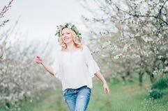 Schöne junge nette schwangere Frau im Kranz von Blumen auf rührendem Hauptbauch, beim gehen im Frühjahr Baum im Garten arbeiten S Stockbilder