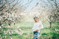 Schöne junge nette schwangere Frau im Kranz von Blumen auf rührendem Hauptbauch, beim gehen im Frühjahr Baum im Garten arbeiten S Lizenzfreies Stockbild