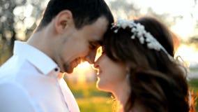 Schöne junge Paarbraut und -bräutigam, die bei Sonnenuntergang umfasst und küsst stock video footage