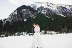 Schöne junge Paare in den Winterbergen Winterweg von Liebhabern Mann, der Frau umarmt lizenzfreie stockfotografie