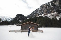 Schöne junge Paare in den Winterbergen Winterweg von Liebhabern Mann, der Frau umarmt stockfoto