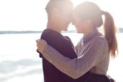 Schöne junge Paare in der Liebe, die auf das Ufer des Sees bei Sonnenuntergang in den Strahlen des hellen Lichtes geht Stockbild
