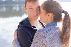 Schöne junge Paare in der Liebe, die auf das Ufer des Sees bei Sonnenuntergang in den Strahlen des hellen Lichtes geht Stockfotos
