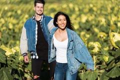 Schöne junge Paare in der Liebe, die auf einem Gebiet von Sonnenblumen steht Stockbilder