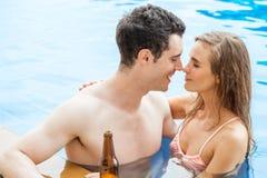 Schöne junge Paare in der Liebe zusammen im Swimmingpool, rubbin lizenzfreie stockfotos