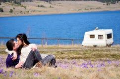 Schöne junge Paare, die auf einer Frühlingswiese mit Krokussen umarmen und sitzen Lizenzfreie Stockfotografie