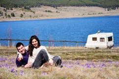 Schöne junge Paare, die auf einer Frühlingswiese mit Krokussen umarmen und sitzen Stockbilder