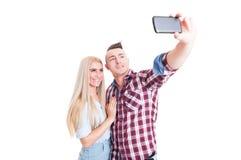 Schöne junge Paare, die ein selfie unter Verwendung des Telefons nehmen Lizenzfreies Stockfoto
