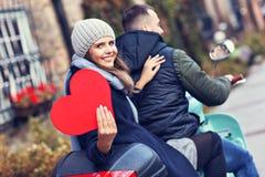 Schöne junge Paare, die Herzen beim Reiten des Rollers in der Stadt im Herbst halten lizenzfreies stockbild