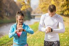 Schöne junge Paare, die ihre Uhren für Lauf im Park vorbereiten Stockfotografie