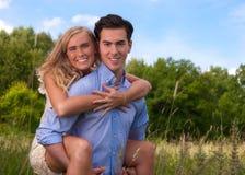 Schöne, junge Paare, die im hohen Gras huckepack tragen Stockfoto
