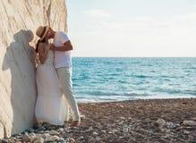 Schöne junge Paare, die nahe dem Felsen umfassen stockfotografie