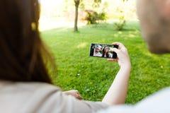 Schöne junge Paare, die selfie beim Sitzen an der Bank im Park nehmen Lizenzfreie Stockfotos