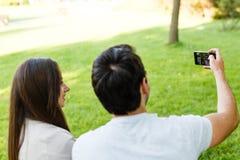 Schöne junge Paare, die selfie beim Sitzen an der Bank im Park nehmen Lizenzfreie Stockbilder
