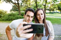 Schöne junge Paare, die selfie beim Sitzen an der Bank im Park nehmen Lizenzfreie Stockfotografie