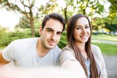 Schöne junge Paare, die selfie beim Sitzen an der Bank im Park nehmen Stockbilder