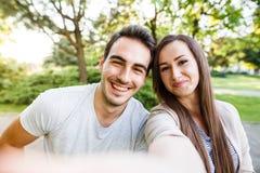 Schöne junge Paare, die selfie beim Sitzen an der Bank im Park nehmen Lizenzfreies Stockfoto