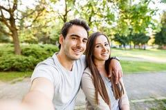 Schöne junge Paare, die selfie beim Sitzen an der Bank im Park nehmen Stockfotos