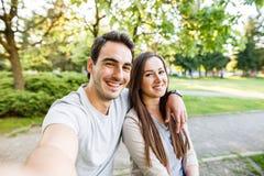 Schöne junge Paare, die selfie beim Sitzen an der Bank im Park nehmen Stockfoto