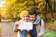 Schöne junge Paare, die selfie im Herbstwald nehmen Stockbild
