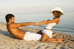 Schöne junge Paare, die Spaß auf der Küste haben Lizenzfreie Stockfotos