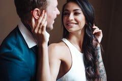 Schöne, junge Paare, die zuhause auf Kamera aufwerfen lizenzfreie stockbilder